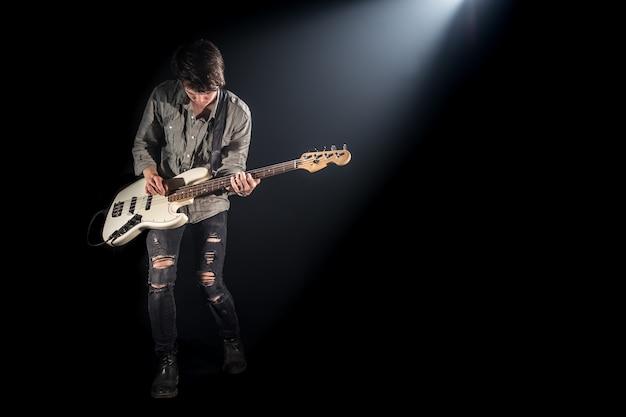 De muzikant speelt basgitaar, op een zwarte achtergrond met een lichtstraal, emotioneel spel, muziekconcept Gratis Foto