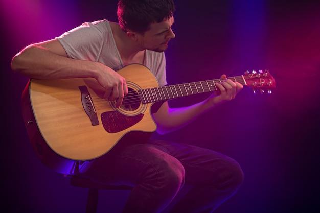 De muzikant speelt een akoestische gitaar. mooie gekleurde lichtstralen. Gratis Foto