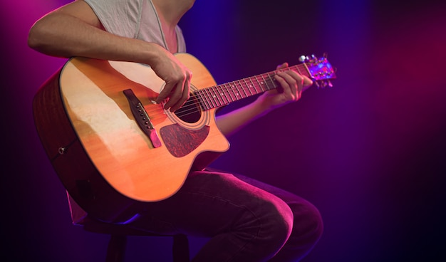 De muzikant speelt een akoestische gitaar. Gratis Foto