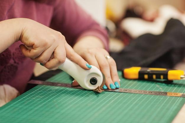 De naai-master knipt een stuk stof af voor verder werk. Premium Foto