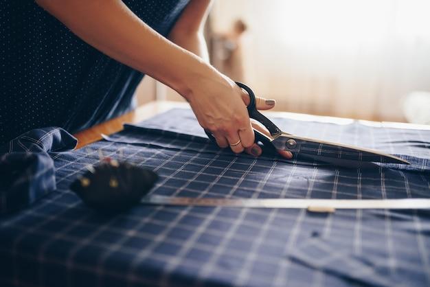 De naaister snijdt de stof voor de jurk. Premium Foto