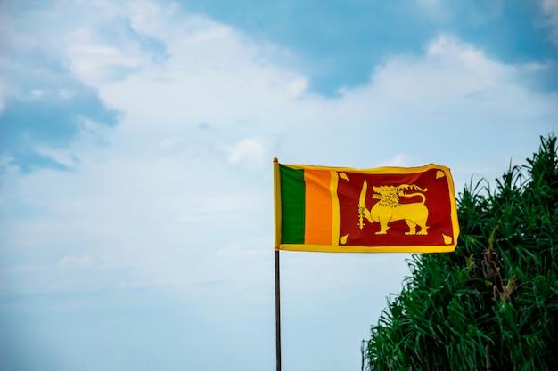 De nationale vlag van sri lanka die tegen blauwe bewolkte hemel met groene struik op de achtergrond vliegt. ruimte voor uw tekst Premium Foto