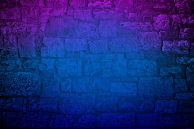 De neon gekleurde achtergrond van de kalksteenbakstenen muur Premium Foto