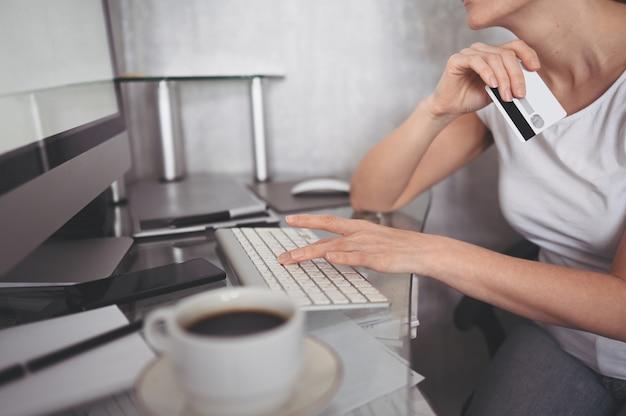 De niet-erkende creditcard van de vrouwenholding in hand en het gebruiken van laptop computertoetsenbord. zakenvrouw of ondernemer werken. online winkelen, e-commerce, internetbankieren, zakgeldconcept Premium Foto