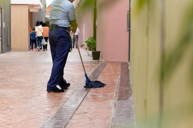 De niet geïdentificeerde vloer van de vrouwen schoonmakende tegel met zwabber. Premium Foto