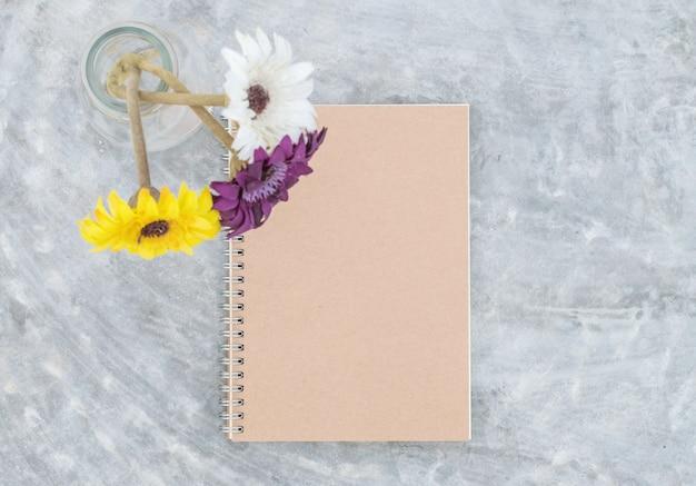 De notaboek van de close-up met kunstmatige kleurrijke bloem op concrete lijstachtergrond Premium Foto