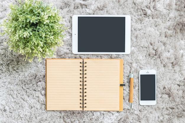 De notaboek van de close-up, tablet, telefoon en kunstmatige installatie op grijze capetachtergrond Premium Foto