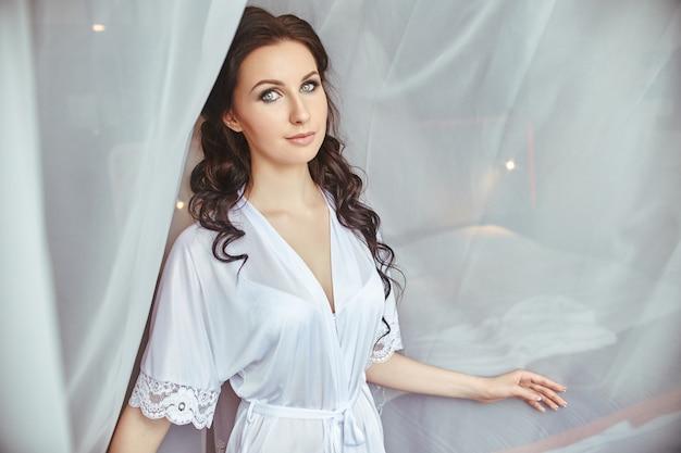 De ochtend van de bruid, een meisje in een zijden gewaad dat bij het raam tegen de witte gordijnen staat Premium Foto