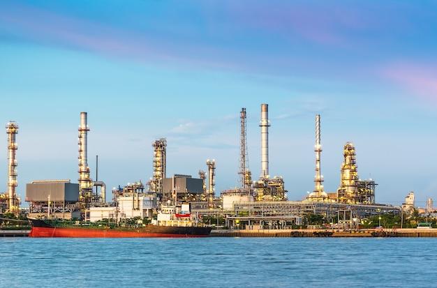 De olieraffinaderij aan de rivier in de schemering Premium Foto