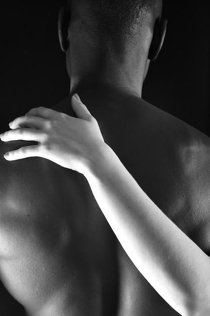 De omhelzing van een interraciaal paar op zwarte achtergrond Premium Foto