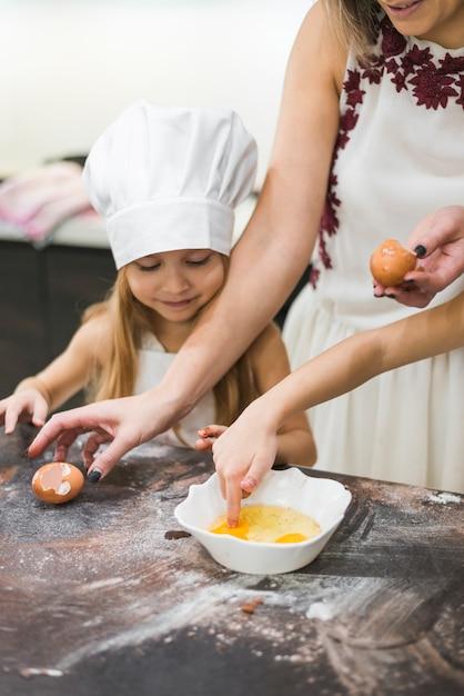 De onderdompelende vinger van het meisje in ei terwijl moeder die voedsel op slordig keukenteller voorbereidt Gratis Foto
