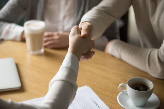 De onderneemster die van het paarhandenschudden overeenkomst in koffie doen, sluit omhoog mening Gratis Foto