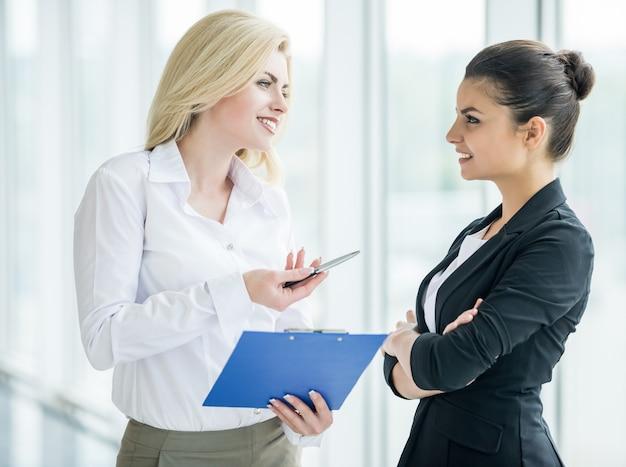 De onderneemsters kleedden formeel bespreken project op kantoor. Premium Foto