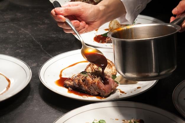 De onscherpe achtergrond van de chef-kok giet de saus op rundvlees is hoofdgerecht. Premium Foto