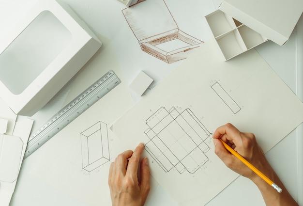 De ontwerper tekent een schets voor kartonnen verpakkingen. maak milieuvriendelijke papieren dozen. Premium Foto