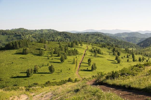 De onverharde weg leidt naar de bergen. Premium Foto