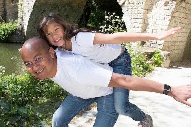 De oorsprong van de indiase of mexicaanse man is een piggyback met zijn dochter Premium Foto