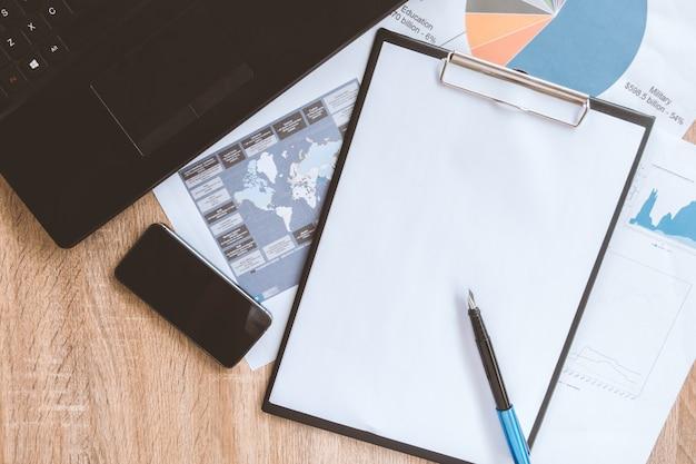 De opgeruimde desktop en het werkhulpmiddelen van de zakenman met administratie, computer, de apparaten van het aanrakingsscherm en kantoorbehoeften op een houten oppervlakte, hoogste mening Premium Foto
