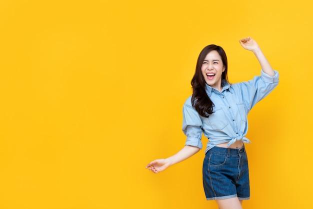 De opgewekte vrij aziatische vrouw die met wapen glimlachen heft op Premium Foto