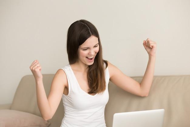 De opgewekte vrouw zegt ja terwijl het kijken op laptop Gratis Foto