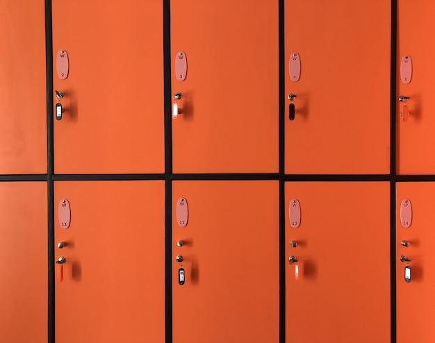 De oranje kluisjes in de sportschool hebben veel deuren vergrendeld met sleutels voor privéveiligheid Premium Foto