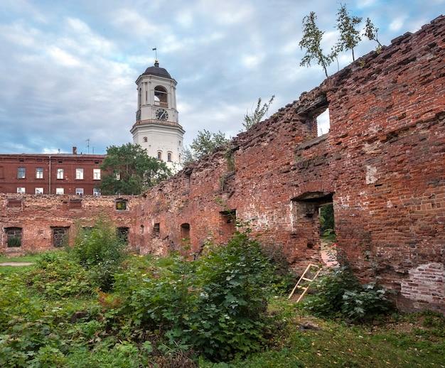 De oude klokkentoren in de stad vyborg rusland door de ruïnes van een tempel Premium Foto
