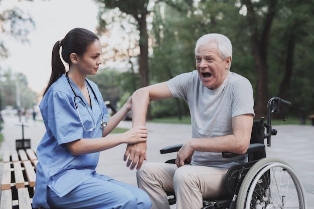 De oude man gaf de zuster om zijn elleboog te onderzoeken die pijn doet Premium Foto