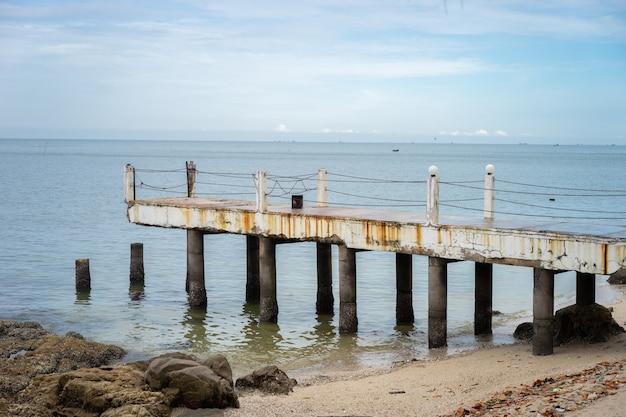 De oude pier ligt naast de rustige, blauwe zee. het is een gevaarlijke plaats om binnen te komen. Premium Foto