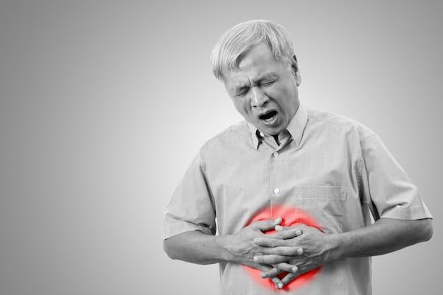 De oudere aziatische mens heeft het concept van de maagpijnpijn met geïsoleerde achtergrond. Premium Foto