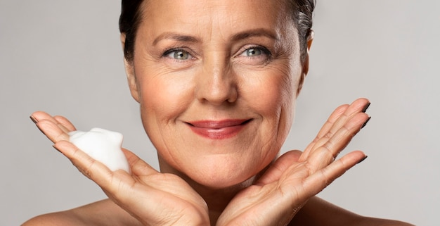 De oudere vrouw van smiley met schuimend reinigingsmiddel in haar hand Gratis Foto