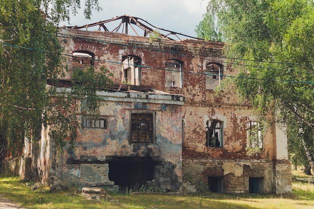 De overblijfselen van een vervallen verlaten stenen huis bedekt met mos en begroeid met bomen in een bos Premium Foto