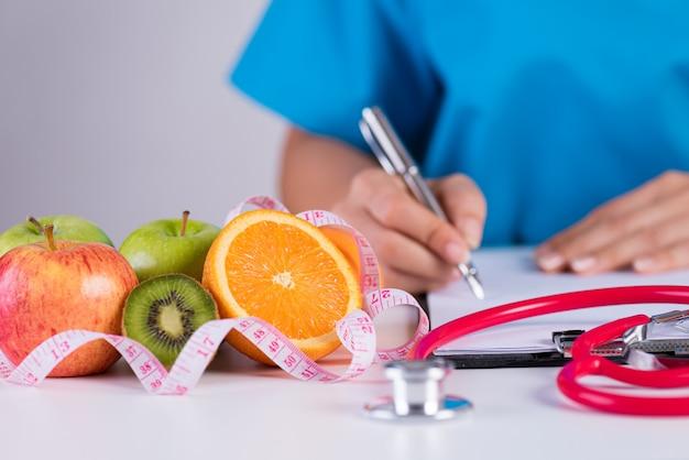 De pen van de artsenholding met controlelijst en groenten, gezondheidszorgconcept. Premium Foto