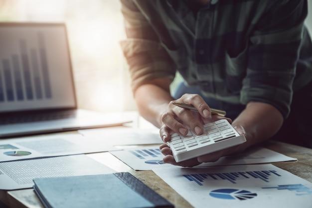 De pen van de bedrijfsmensenholding met het gebruiken van calculator om balans jaarlijks met het gebruiken van laptop computer aan het berekenen van begroting te herzien. audit en controleer integriteit voor investeringsconcept. Premium Foto