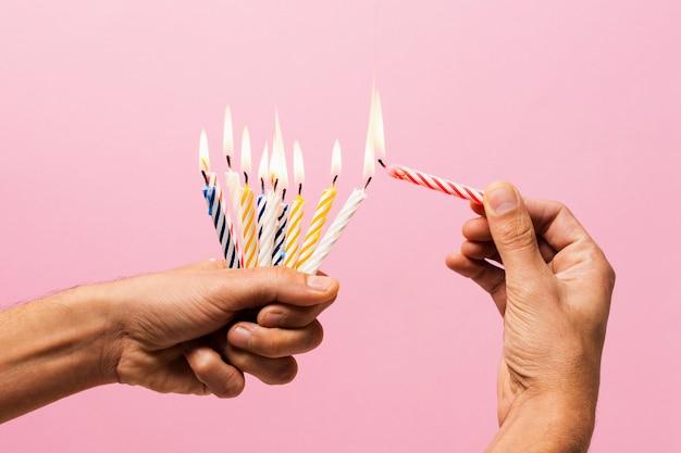De persoonsholding stak verjaardagskaarsen aan Gratis Foto
