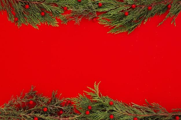 De pijnboombladeren van kerstmis op een rode kaderachtergrond met copyspace Gratis Foto