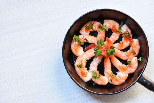 De plaat van zeevruchten met garnalen garnalen oceaan gastronomisch verfraait dinerlijst met sauskruiden en kruiden op pan wordt gekookt die Premium Foto