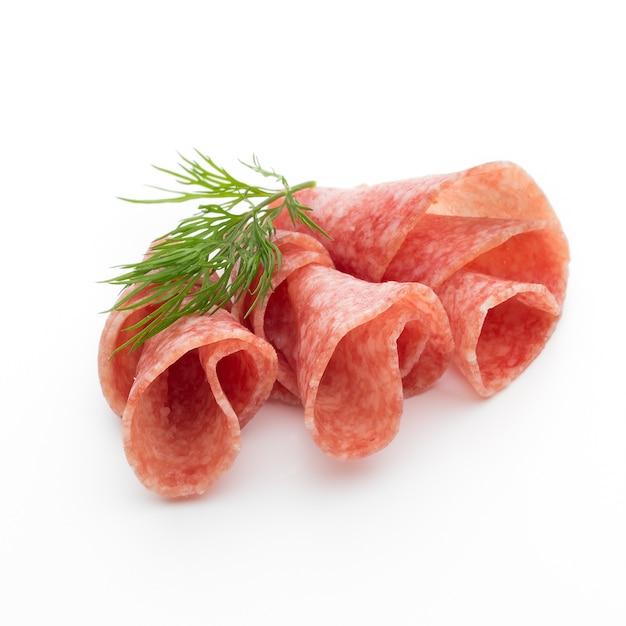 De plakjes van de salamiworst die op wit lijstknipsel worden geïsoleerd Premium Foto