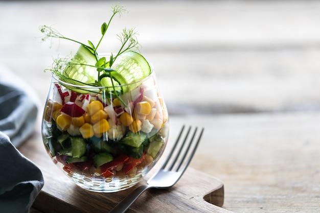 De plantaardige salade van de lente in een glaskop op een houten achtergrond. goede voeding. kopieer ruimte. verticaal. selectieve aandacht. Premium Foto