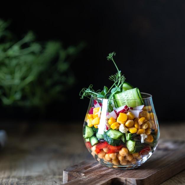 De plantaardige salade van de lente in een glaskop op een houten achtergrond. goede voeding. kopieer ruimte. vierkant. selectieve aandacht. Premium Foto