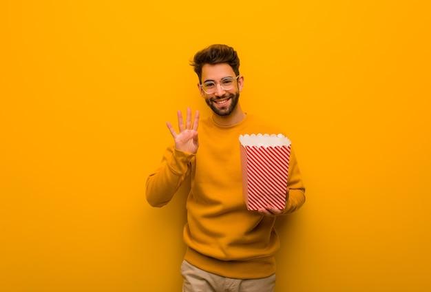 De popcorns die van de jonge mensenholding nummer vier tonen Premium Foto