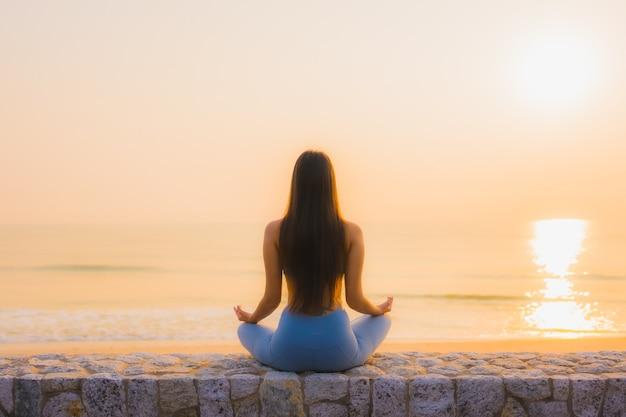 De portret jonge aziatische vrouw doet meditatie rond overzeese strandoceaan bij zonsopgang Gratis Foto