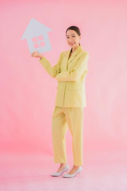 De portret mooie jonge aziatische bedrijfsvrouw toont huis of huisteken op geïsoleerde kleur Gratis Foto