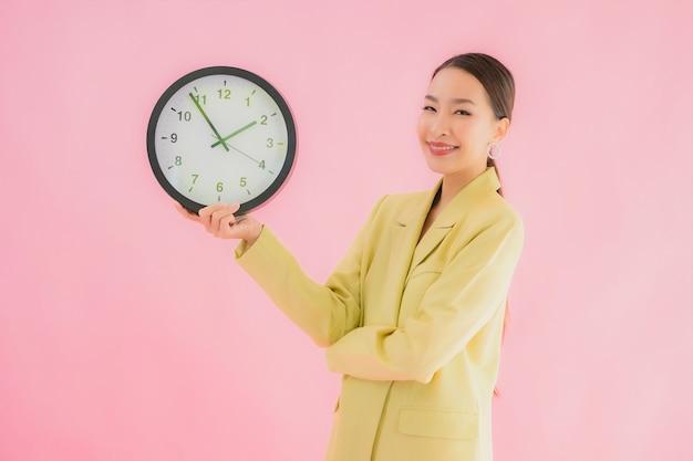 De portret mooie jonge aziatische bedrijfsvrouw toont klok of alarm op geïsoleerde kleur Gratis Foto