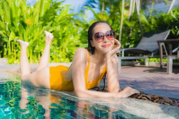 De portret mooie jonge aziatische vrouw ontspant gelukkige glimlach rond openluchtzwembad in hoteltoevlucht voor vrijetijdsvakantie Gratis Foto