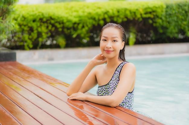 De portret mooie jonge aziatische vrouw ontspant glimlach rond openluchtzwembad voor vrije tijd en vakantie Gratis Foto