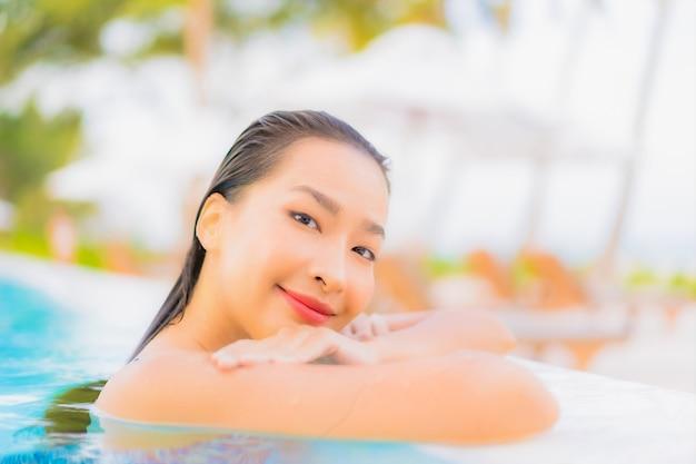 De portret mooie jonge aziatische vrouw ontspant vrije tijd rond openluchtzwembad met overzees oceaanstrand Gratis Foto
