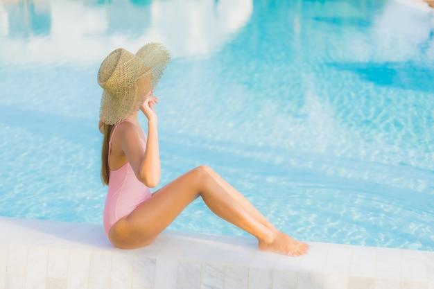 De portret mooie jonge aziatische vrouw ontspant vrije tijd rond openluchtzwembad met overzees Gratis Foto