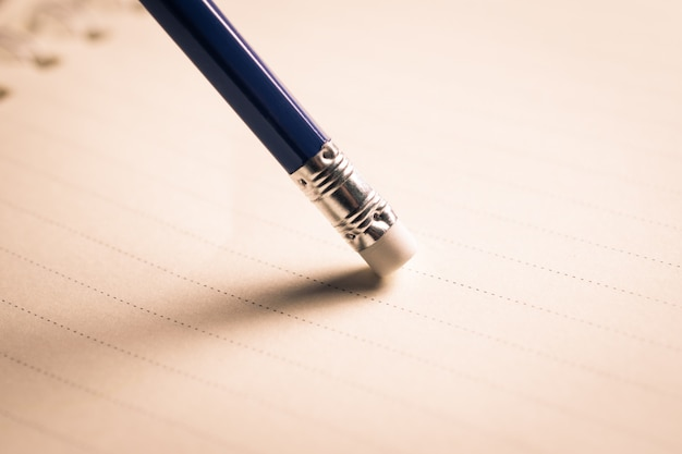 De potloodgom die een geschreven fout op een stuk van document verwijdert, schrapt, corrigeert en ontwerpt fout. Premium Foto