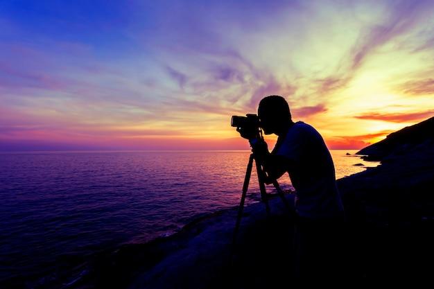 De professionele fotografiemens neemt een van de fotozonsondergang of zonsopgang dramatische hemel over het tropische overzees in phuket thailand Premium Foto