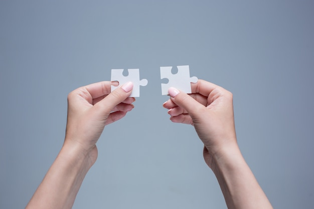 De puzzels in handen op grijs Gratis Foto